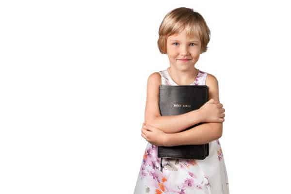 young girl holding bible - memorize the books of the Bible