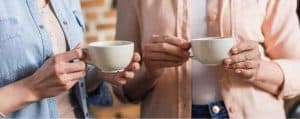 two women holding coffee cups - homeschooling with depression