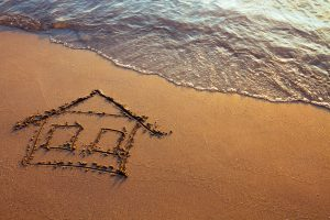 Drawing of a simple house in the sand with water lapping nearby