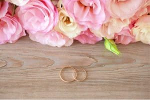 flowers with wedding rings on wood