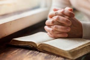 Woman by window with hands praying over a Bible