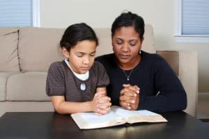 praying mom with young child